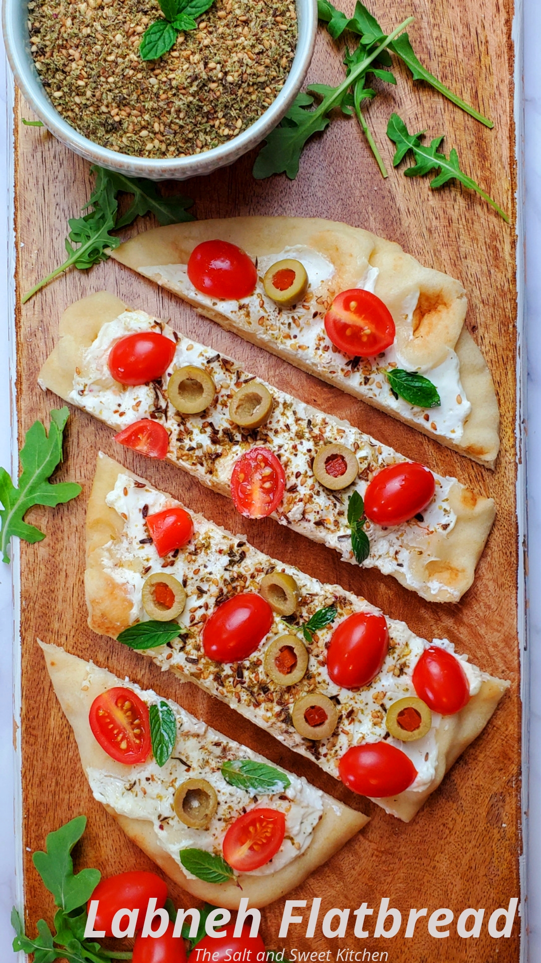 Are you looking for naan flatbread recipes? This Labneh flatbread topped with labneh spread, olives, zaatar and mint is a must try!