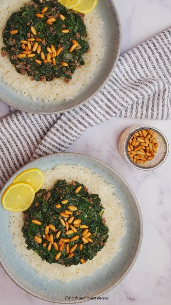 Lebanese spinach stew (sabanekh) served over rice with lemon slices and pine nuts.