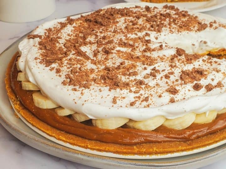 banoffee pie on a white plate with digestive biscuits