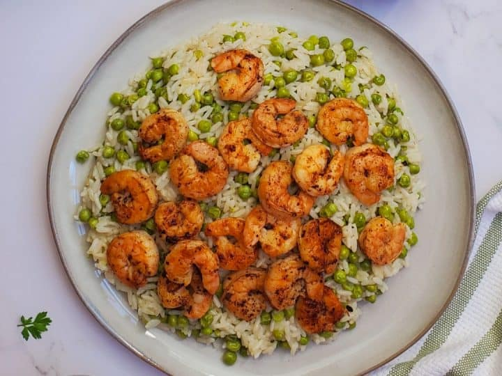 Shrimp and rice with peas in a white plate