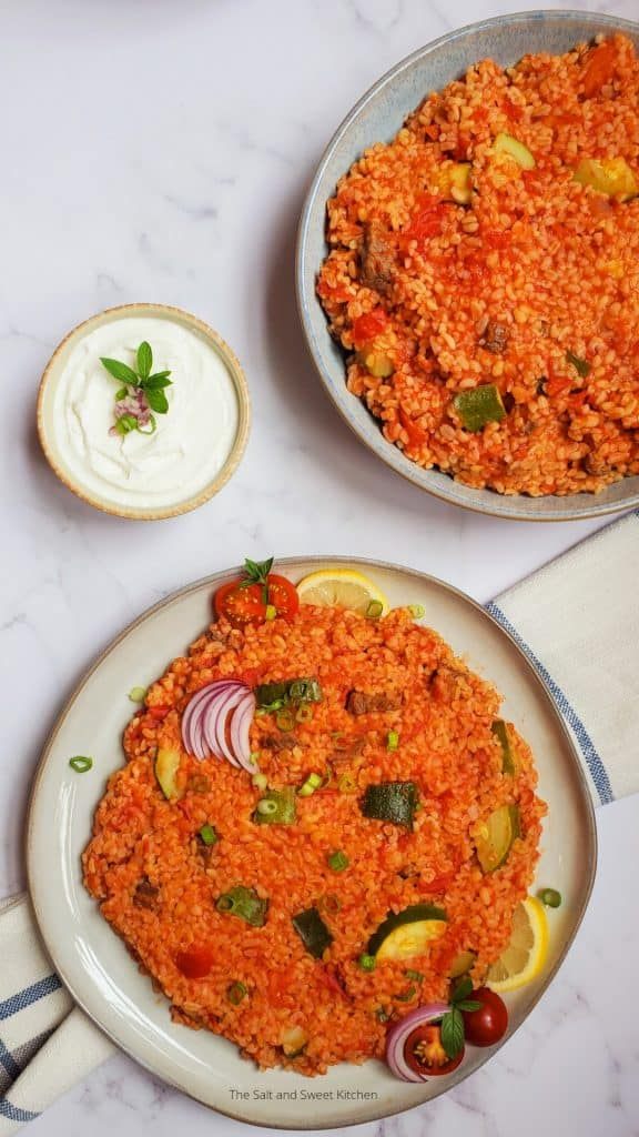 bulgur pilaf with zucchini on a serving plate with a cup of plain yogurt